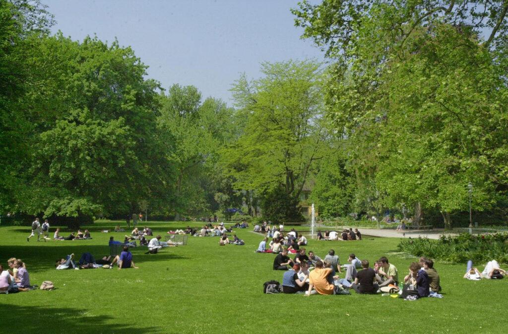 Viele Leute bevölkern den sommerlichen Stadtpark.