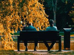 Parkbank mit zwei Menschen